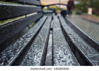 Water drops after a rain on a bench on a blurred background of the street