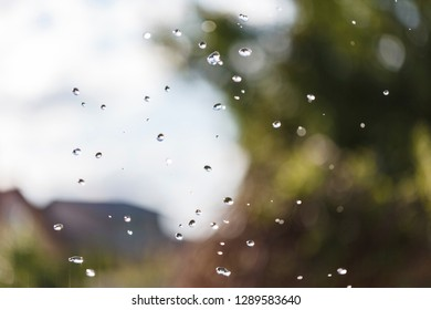 The water drops in the air against the sky