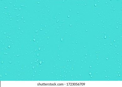Water drops on blue background. Liquid droplets on bright color plastic surface. Raindrops texture. Abstract wet dewy background