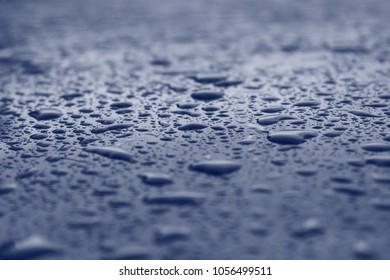 Water drops on blue surface. A macro photograph with very shallow depth of field.