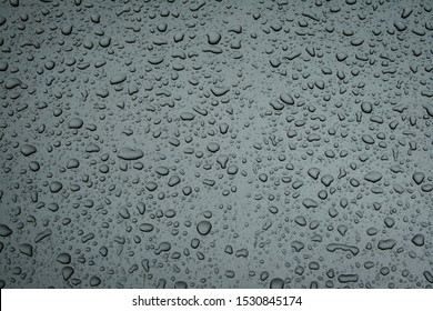 Water drops on the bonnet hood of a metallic gray car