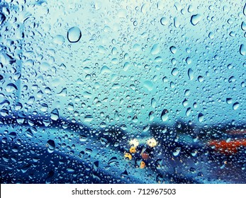Water drops on a car glass window while driving in rainy weather