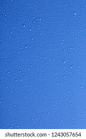 Water drops on color background, top view