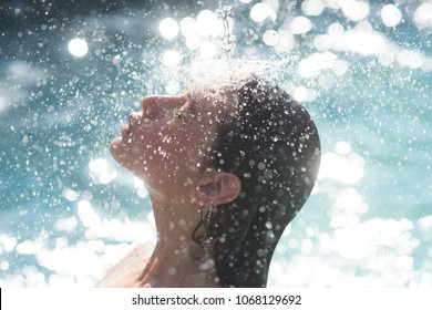 water drops on face of young woman. water bathing in swimming pool.