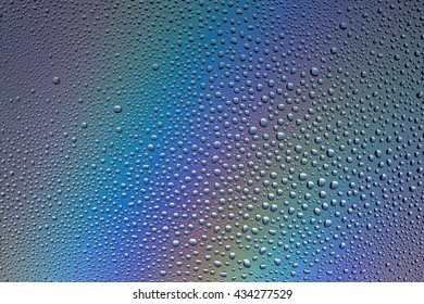 Water drops on glass background in red-violet light
