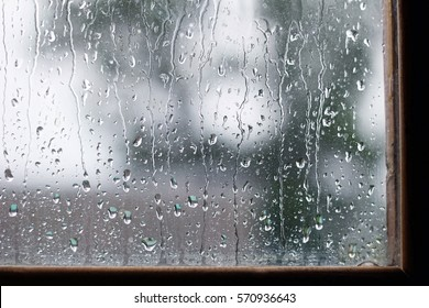 water drops on glass in rainy day. rain outside window on summer or autumn season. texture of raindrops close up, wet glass.