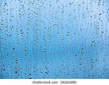 Water drops on glass texture or background. Blue tint.