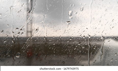Water drops on the glass. Drops trickle down the window of the plane, rain on the runway. Flying on a plane in cloudy weather with precipitation. Template.