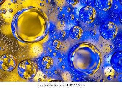 Water drops on glass with a yellow and blue lighted background