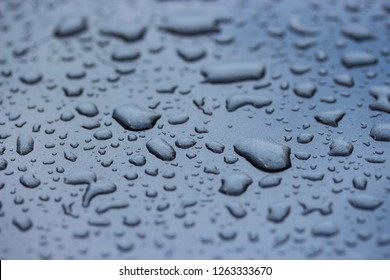 Water drops on gray metal sheet after rainy day