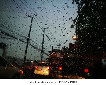 Water drops on the pane of glass with road background.traffic jam background.