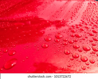 Water drops on the red car surface background.