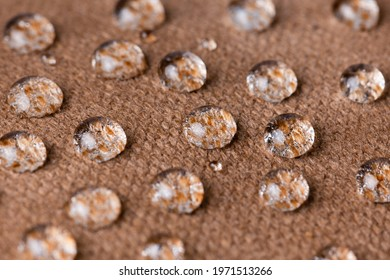 Water drops on waterproof biege or brown fabric close-up. Water resistant textile.