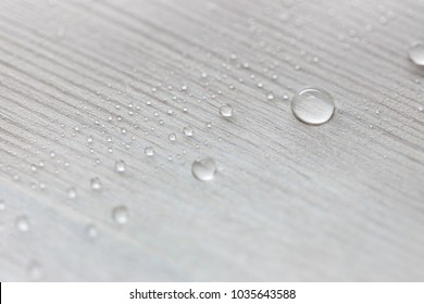 Water drops on white wooden surface made from larch wood covering by oil with wax.