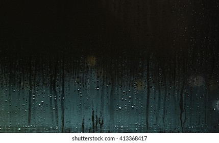 Water drops on window with blue-green glow