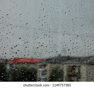 Lot of water drops on window. Gray sky behind. Rainy day, wet glass. Blurred city behind.