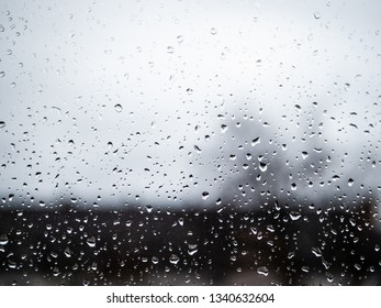 Water Drops on a window with grey skies and silhouettes of houses in background