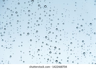 Water drops on window making stunning bubble formation and texture with reflection of outdoor scenery with field. Concept: fresh, bubbly, sprinkle, gas, air, rising