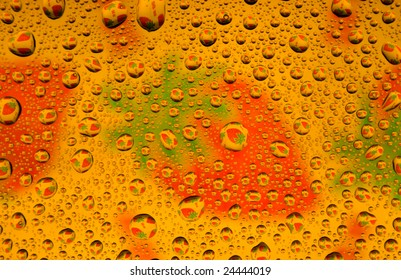 Water drops over strawberries background (close-up photo)