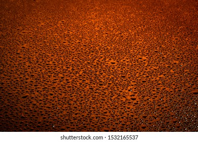 Water drops texture on dark surface with orange lights.
