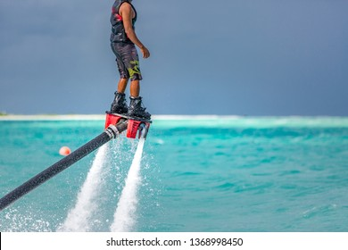 Water extreme sport, summer sea and tropical weather with outdoors active people enjoying water sports. Fly board, surfing in ocean, fun and summer recreational activity. Flyboarding and seariding