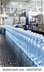 Water factory - Water bottling line for processing and bottling pure spring water into small blue bottles. Selective focus.