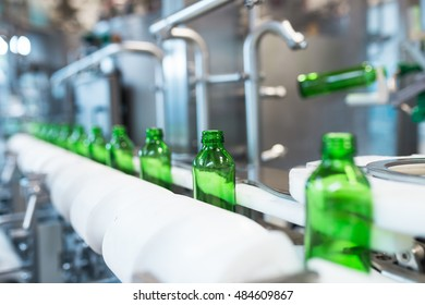 Water factory - Water bottling line for processing and bottling pure mineral water into small green glass bottles. Selective focus.