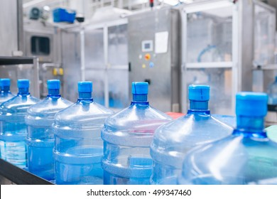Water factory - Water bottling line for processing and bottling pure spring water into blue gallons. Selective focus.