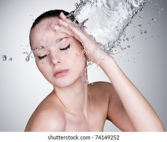 Water falling on the beautiful sensuality woman face with clean skin - horizontal