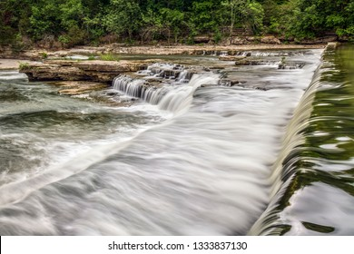 Water falls over an old mill dam and cascades over rocky limestone ledges at Upper Cataract Falls in Owen County, Indiana.