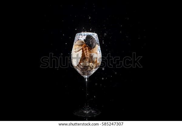 Water falls in wineglass full of shells