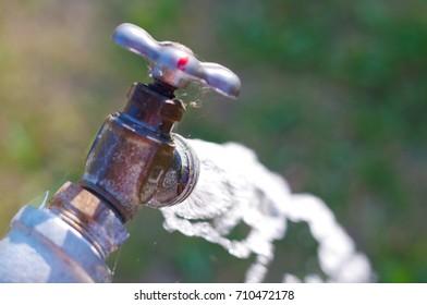 Water faucet running water outside closeup