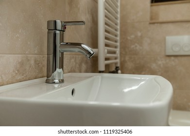 Water faucet/Chrome and shiny water tap faucet in a stylish creamy marble bathroom.
