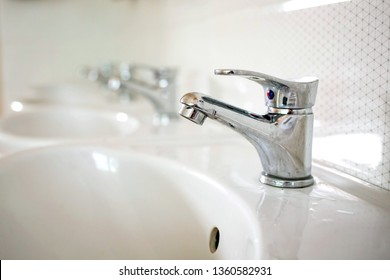 Water faucets with white sinks in the bathroom isolated