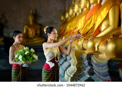 Water festival. Asia woman wearing Thai tradional costume Buddha Bathing in Songkran day water festival at Thailand.