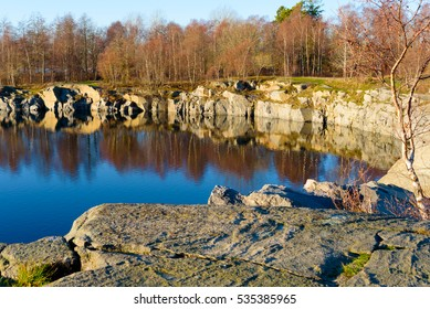 Water filled granite stone quarry in leafless forest in winter. Location Torko island near Ronneby, Sweden.