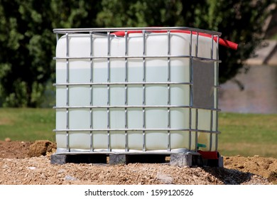 Water filled white intermediate bulk container or IBC plastic tank with metal cage put on top of gravel pile at local construction site surrounded with dense trees in background