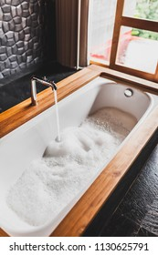 Water filling bath with foam. Modern style of bathroom with wooden edge and black walls