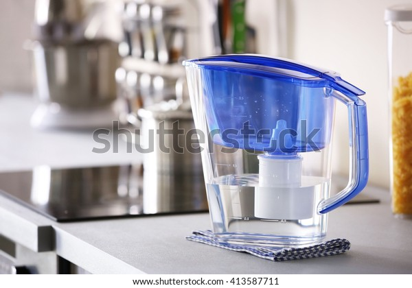 Water filter jug with napkin on kitchen table