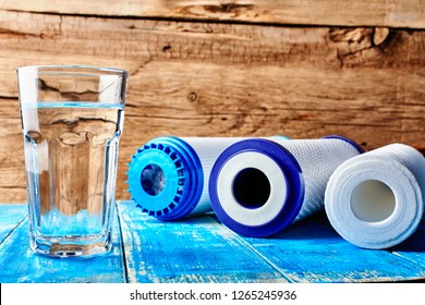 Water filters. Carbon cartridges and a glass of water on a wooden background. Household filtration system.
