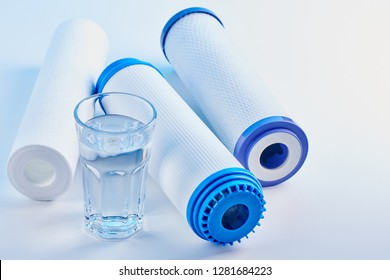 Water filters. Carbon cartridges and a glass on a white background. Household filtration system.