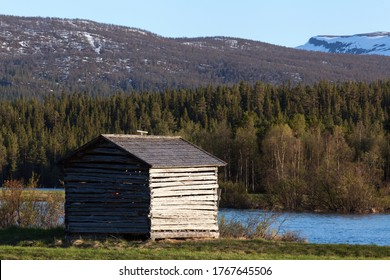 Water from a flooded river cover a delta land. Wooden barns on the meadows.