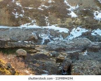 Water flow in nearby river near Hraunfossar waterfall with snow and ice in winter season, Iceland