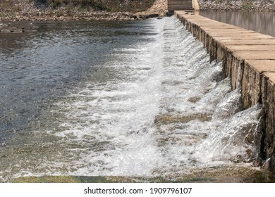 The water flow passes the weir from upper level to lower level the side stream of the river. The weir forms a small waterfall. - Shutterstock ID 1909796107