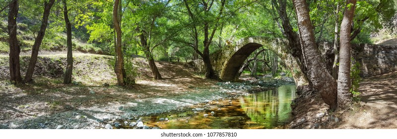 "Water flowing in a mountain river creating small waterfalls.The old Venetian bridge of Kelefos (or ""Tzielefos""), Troodos mountain, district of Limassol (Cyprus). Panoramic photo."