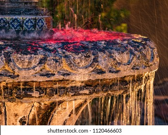 Water flowing in a neon-lit fountain made of carved stone