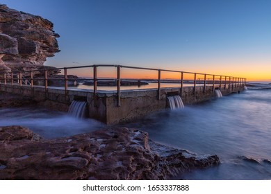 Water flowing from North Curl Curl rock pool at sunrise.