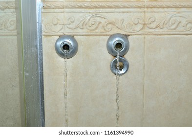 Water flowing out from pipelines on a bathroom wall