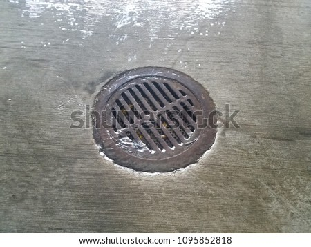 water flowing over cement into metal drain on floor