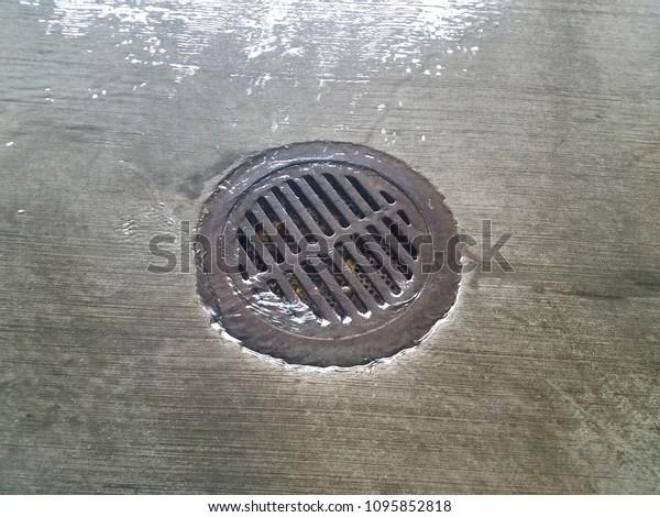 water flowing over cement into metal drain on floor